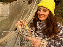 Women mend a fishing net. Attractive smiling brunette fishing woman - with a cap mend a her fishing net in the late afternoon sun. Horizontal color photo Stock Images