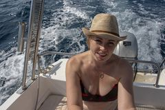 Women in mid 40`s driving a small boat. She wears a hat stock photography