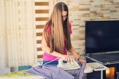Women with modern plastic pink shirt ironing in modern house.  royalty free stock photos