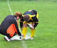 Women Moravian-Silesian football league, injury. FOOTBALL PITCH DOBRA, CZECH REPUBLIC - MAY 10: Team doctor treats injury footballer in match in Women Moravian Stock Image