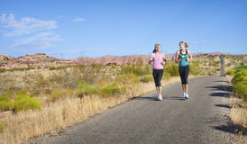 Women on a morning jog together. Two beautiful middle-aged female joggers training running along a beautiful desert landscape. lots of copy space Stock Images