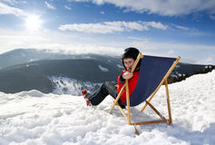 Women at mountains in winter lies on sun-lounger Stock Photography