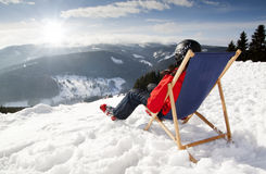 Women at mountains in winter lies on sun-lounger Royalty Free Stock Image