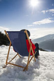 Women at mountains in winter lies on sun-lounger Royalty Free Stock Photography