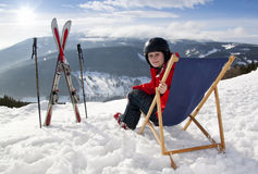 Women at mountains in winter lies on sun-lounger Royalty Free Stock Images