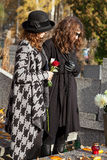 Women in mourning at cemetery in autumn Stock Image