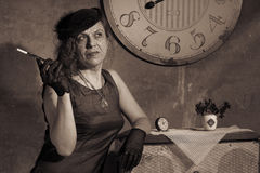 Women with mouthpiece. Redhead woman with mouthpiece near the clock. Photo in old image style. Sepia royalty free stock image