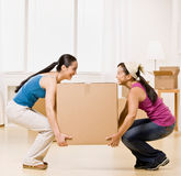 Women moving into new home and carrying box Stock Photo