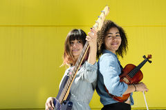 Women musicians standing back to back with instruments Royalty Free Stock Images