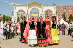 Women in national costumes dance in a circle, holding hands stock photo