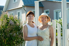 Women near fence wicket of home Stock Photography
