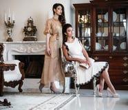 Women near fireplace in luxury interior Royalty Free Stock Photo