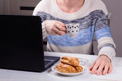 Women in the office drinking morning coffee with profiteroles. Coffeebreak during the working day. Women designer in the office drinking morning coffee with stock photography