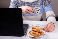 Women in the office drinking morning coffee with profiteroles. Coffeebreak during the working day stock photo