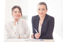 Women in office. Two  attractive friendly young businesswomen talking and smiling to each other at informal meeting in modern office Stock Photography