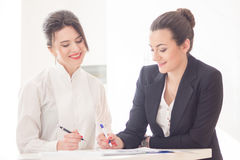 Women in office. Two  attractive friendly young businesswomen talking and smiling to each other at informal meeting in modern office Royalty Free Stock Images