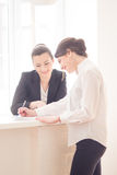 Women in office. Two  attractive friendly young businesswomen talking and smiling to each other at informal meeting in modern office Royalty Free Stock Photos
