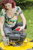Women oiling yellow lawn mover Stock Photography