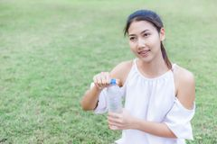 Women open bottle in the park after exercise stock photo