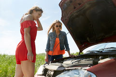 Women with open hood of broken car at countryside Royalty Free Stock Images