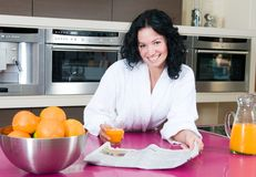Women with orange juice at kitchen Stock Images