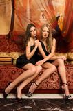 Women in orient interior. Two beautiful women are sitting on the sofa in a oriental interior Royalty Free Stock Photos