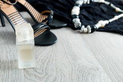Women outfit. Black lace dress, shoe sandals, necklace and perfume on grey wooden background. Evening accessory for party. Copy sp Stock Photography