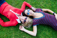 Women Outside. Two young attractive women lying together on the grass Royalty Free Stock Photos