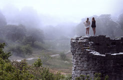 Women Overlooking Bright Foggy Valley. Young women overlooking beautiful, foggy valley from an ancient ruin Royalty Free Stock Photography