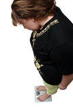 Women with overweight looking on scales Royalty Free Stock Images