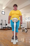 Women with overweight on scales in gym Stock Images