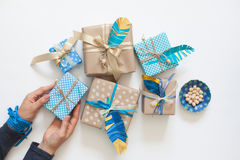 Women pack gifts in kraft paper tape. View from above. Preparation for the holiday. Gift wrapping stock photos