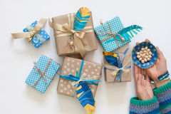 Women pack gifts in kraft paper tape. View from above. Gifts turquoise and blue. Decorative feathers adorn gifts stock photo