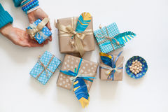 Women pack gifts in kraft paper tape. View from above.v. Women pack gifts in kraft paper tape. View from above. Gifts turquoise and blue. Decorative feathers royalty free stock image