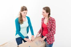 Women packing the cardboard box. Close-up of smiling young women packing the cardboard box against white background stock image