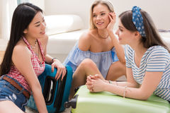 Women packing luggage for vacation together at home, getting ready to travel concept Royalty Free Stock Photo