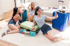 Women packing suitcases for vacation and taking travel selfie on smartphone at home, packing luggage concept Royalty Free Stock Photo