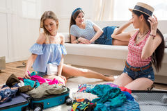 Women packing suitcases for vacation together at home, getting ready to travel concept Stock Images