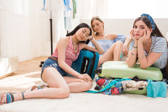 Women packing suitcases for vacation together at home, packing luggage concept Stock Image