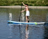 Women Paddle Boarder. This is a Summer picture of a female paddle boarder working out on the Lincoln Park Lagoon located in Chicago, Illinois in Cook County Royalty Free Stock Photo
