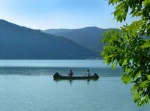 Women paddling canoe on lake royalty free stock images