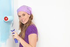 Women painting nursery wall. Young woman painting nursery wall blue Royalty Free Stock Photos