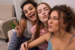 Women in pajamas on sofa. Three nice girls looking at camera and smiling. Having pajamas party Stock Photos