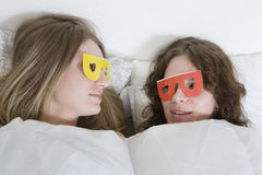 Women with paper glasses lying on bed Royalty Free Stock Photos