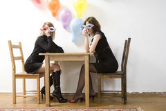 Women with paper glasses sitting at table Stock Images