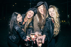 Women partying outdoors. Pretty women toasting champagne glasses and having fun - Four girls drinking sparkling white wine and celebrate before going into club stock photo