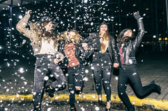 Women partying. Pretty crazy girls dancing, throwing confetti and having fun - Young women partying outdoors before to go in a club royalty free stock photo
