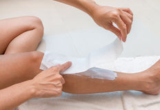Women are pasting fabric for waxing legs. Royalty Free Stock Images
