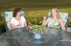 Women on Patio Laughing with Wine. Two pretty women laughing over a glass of wine on the patio royalty free stock photos