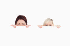 Women peeking over a banner. In a studio Royalty Free Stock Image